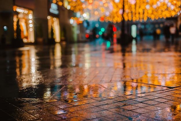 Regnerische nacht in einer großstadt, reflexionen von lichtern auf der nassen fahrbahn.