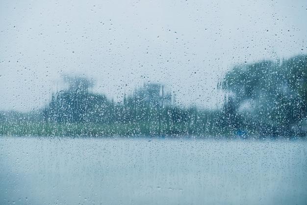 Regnerischer tageskonzept. regentropfen auf glasfenster. fluss und baum in der landschaft