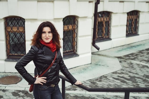Regnerisches porträt des schönen nachdenklichen mädchens mit dem gelockten braunen haar in der schwarzen lederjacke, in den blauen jeans, im roten schal und in der roten handtasche