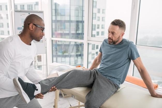 Rehabilitationsbehandlung. netter angenehmer mann, der in der arztpraxis sitzt, während er muskeln seines beines entwickelt