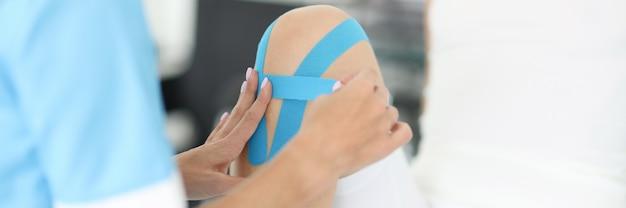 Rehabilitationstherapeut, der blaue bänder auf das knie der frau klebt, nahaufnahme