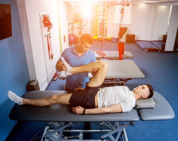 Rehabilitationstherapie. physiotherapeut arbeitet mit jungen männlichen patienten
