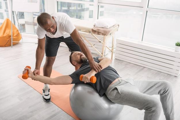 Rehabilitationszentrum. ernsthafter qualifizierter coach, der mit einem patienten im rehabilitationszentrum arbeitet