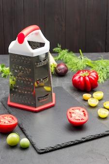 Reibe und rote tomatenscheiben auf schneidebrett. pfeffer und dill auf dem tisch. schwarzer hintergrund. ansicht von oben