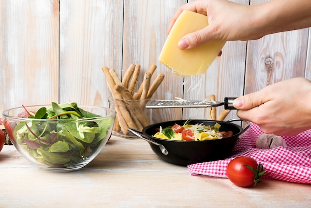 Reibender käse der hand der person über teigwaren in der küche