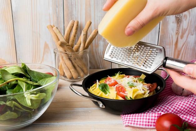 Reibender käse der person über frischen gekochten spaghettis im behälter mit gemüse auf worktop