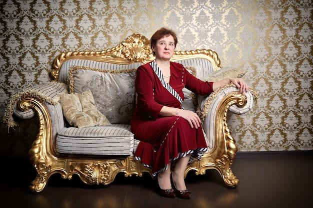 Reiche ältere frau, die auf einem teuren sofa sitzt
