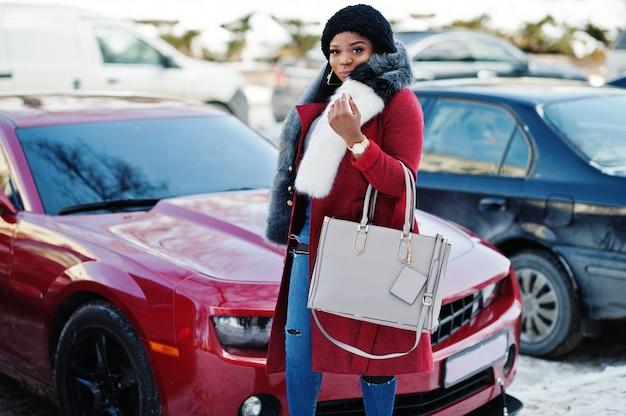 Reiche afroamerikanerfrau im roten mantel und im pelz gegen rotes muskelauto. schwarze stilvolle erfolgreiche geschäftsfrau.
