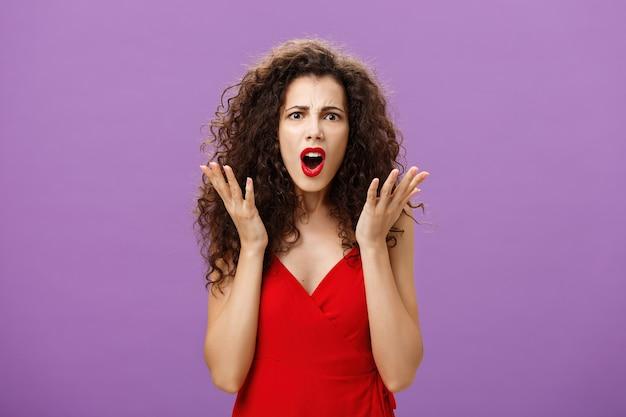 Reiche arrogante und snobistische europäische frau mit lockiger frisur in rotem abendkleid, die mit stirnrunzeln streitet, verwirrt und unzufrieden zitternde handflächen in enttäuschung posiert über lila wand.