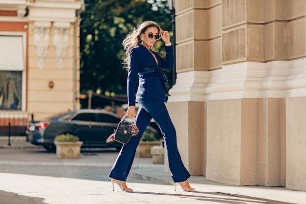 Reiche luxusfrau gekleidet in elegantem stilvollem blauem anzug, der in der stadt am sonnigen herbsttag hält geldbörse geht