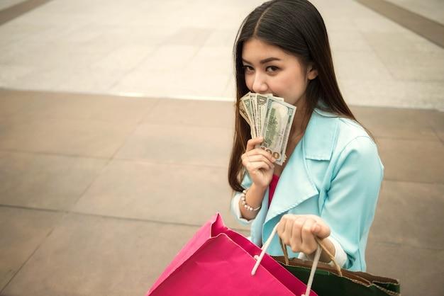 Reiche shopaholic schöne frau mit banknoten
