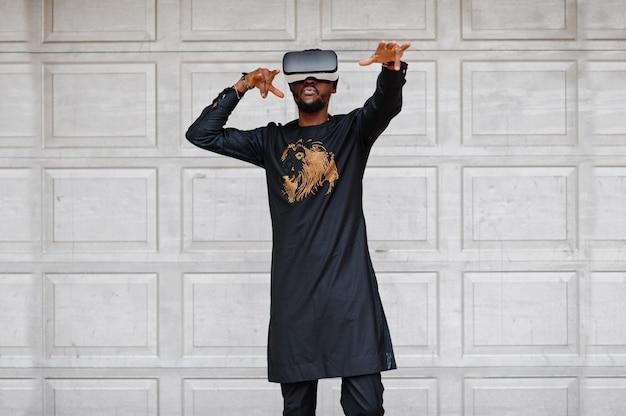 Reicher afrikanischer mann in der stilvollen traditionellen kleidung in vr gläsern. zukunft afrikas konzept.