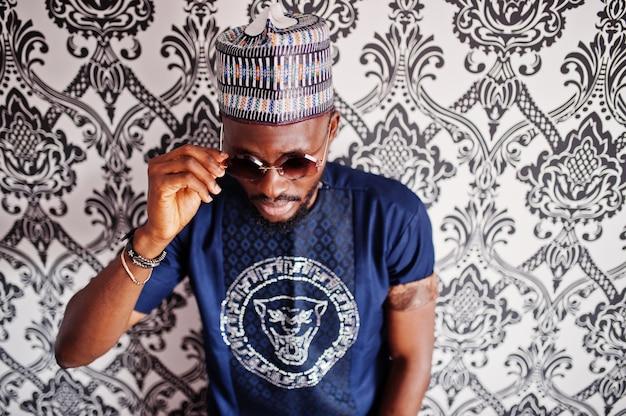 Reicher afrikanischer mann in der stilvollen traditionellen kleidung und im hut in den gläsern warf am studio gegen weinlesehintergrund auf.