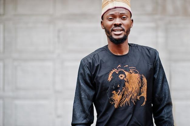 Reicher afrikanischer mann in der stilvollen traditionellen kleidung und im hut warf gegen garagentore auf.