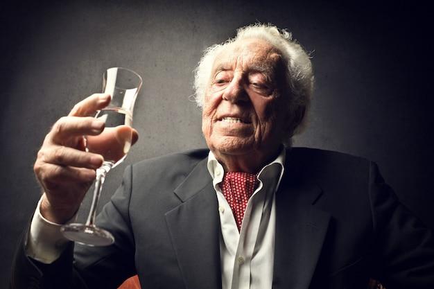 Reicher alter mann, der etwas trinkt