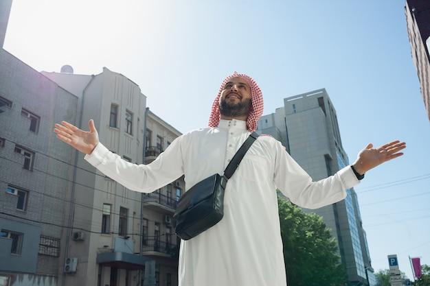 Reicher arabischer mann, der immobilien in der vielfalt der ethnischen kultur der stadt kauft