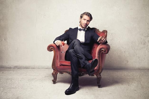 Reicher eleganter mann, der in einem lehnsessel sitzt