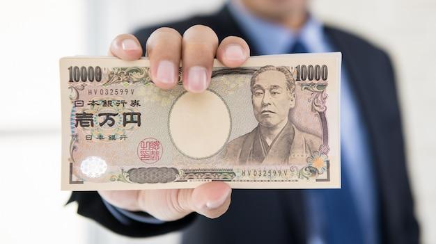 Reicher geschäftsmann, der geld der japanischen yen zeigt