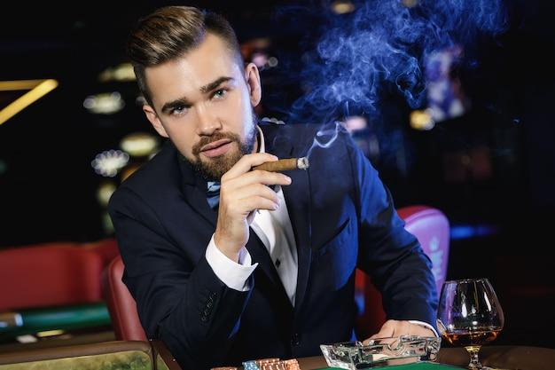 Reicher gutaussehender mann, der im kasino zigarre raucht