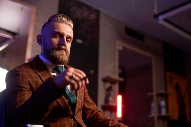 Reicher junger kaukasischer geschäftsmann im anzug rauchen eine zigarre, während er allein im dunklen raum sitzt