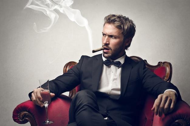 Reicher rauchender geschäftsmann