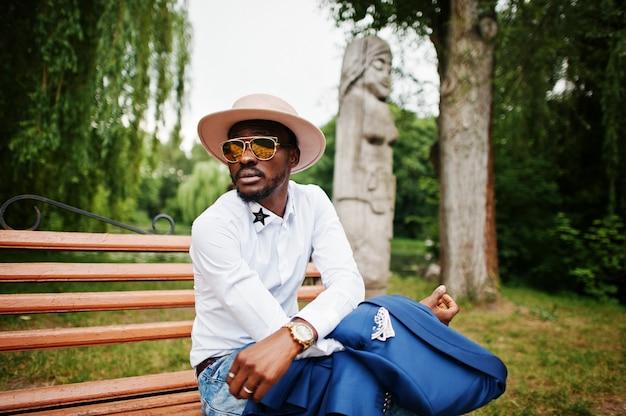 Reicher schwarzer mann, der auf bank an der goldenen sonnenbrille und am hut sitzt