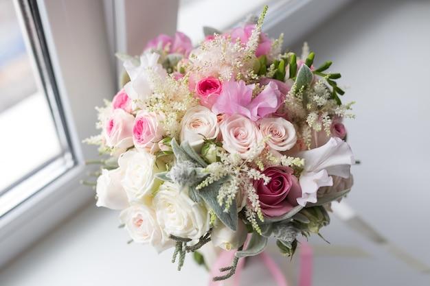 Reicher strauß rosa pfingstrosen und lila eustoma-rosenblumen, grünes blatt im fenster. frischer frühlingsstrauß. sommer hintergrund