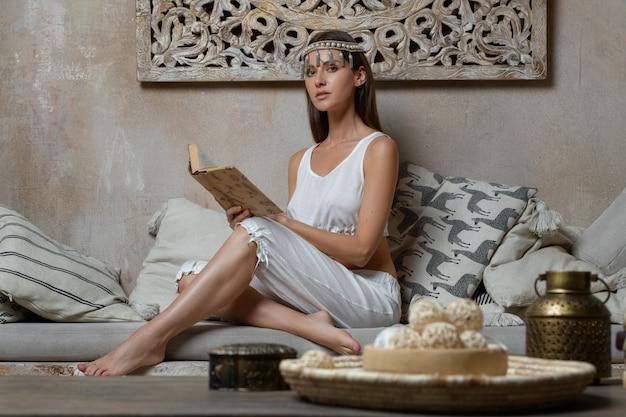 Reiches braunes haar in der kranzfrau shaherezada, die märchenbuch mit den langen nackten barfüßigbeinen auf steinbank mit kissen im luxusinnenbadekurorthaus der arabischen art der wüste mit krug auf tabelle sitzt und liest