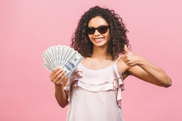 Reiches mädchen! geldgewinner! überraschte schöne afroamerikanerfrau im kleid, das geld hält und die kamera lokalisiert gegen rosa hintergrund betrachtet. daumen hoch.