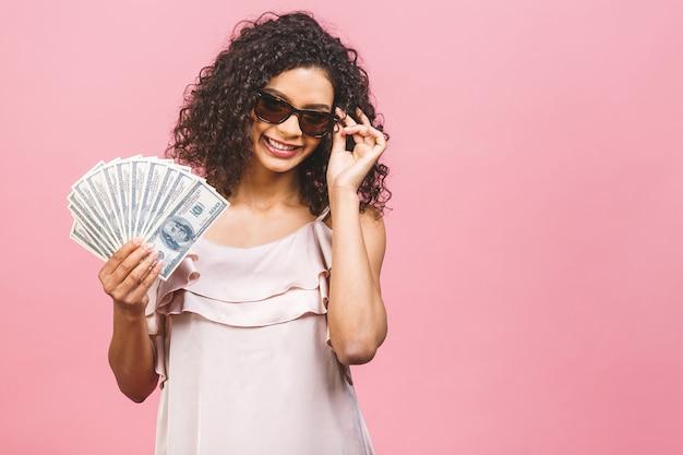 Reiches mädchen! geldgewinner! überraschte schöne afroamerikanerfrau im kleid, das geld hält und die kamera lokalisiert gegen rosa hintergrund betrachtet.