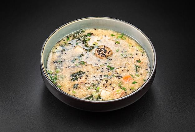 Reichhaltige kim chi suppe mit forelle, tofu. wakame seetang, reis, hühnerei und sesam.