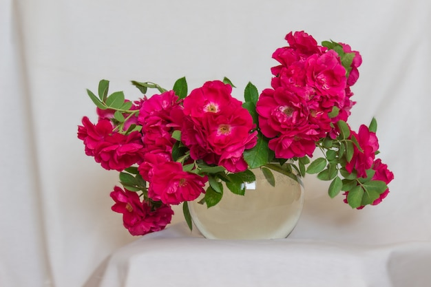 Reichhaltiges bouquet von tees, rosa rosen in einer glasvase