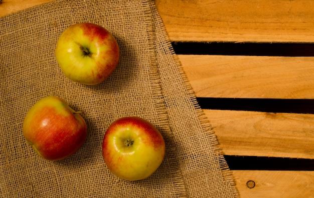 Reife äpfel auf sackleinen und hölzernen platten, platz für text, draufsicht