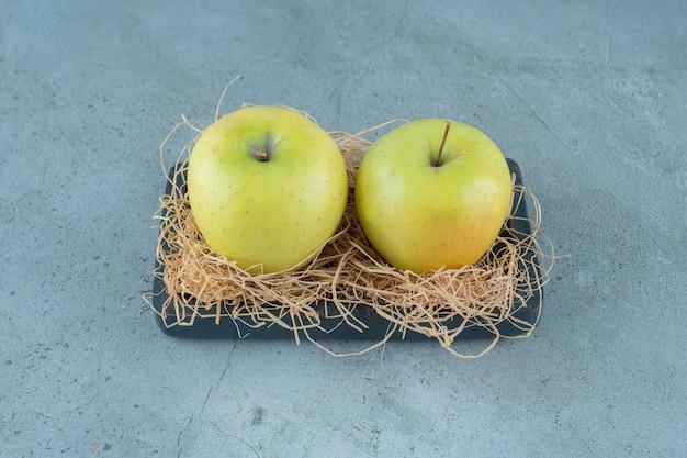 Reife äpfel auf trockenem stroh und auf einem brett auf dem marmorhintergrund. foto in hoher qualität