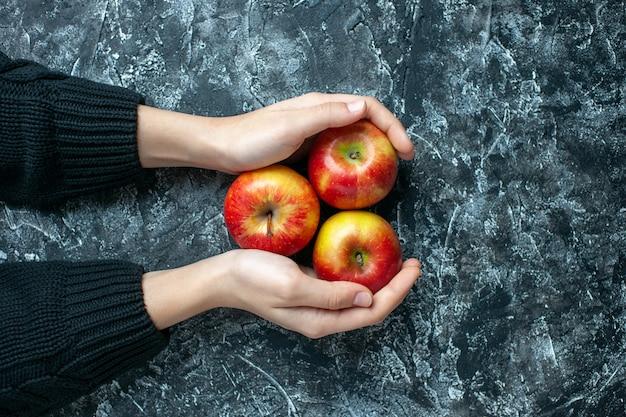 Reife äpfel der draufsicht in weiblichen händen auf grauem hintergrund mit kopienplatz