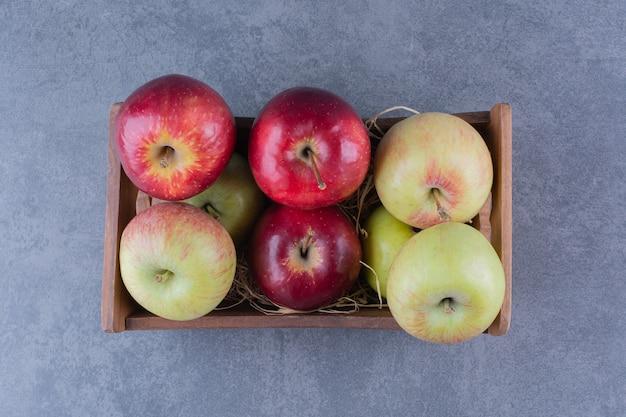 Reife äpfel im karton auf der dunklen oberfläche