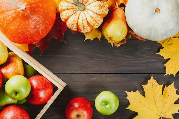 Reife äpfel in einem kasten mit kürbisen, äpfeln und birnen auf dunklem hölzernem.
