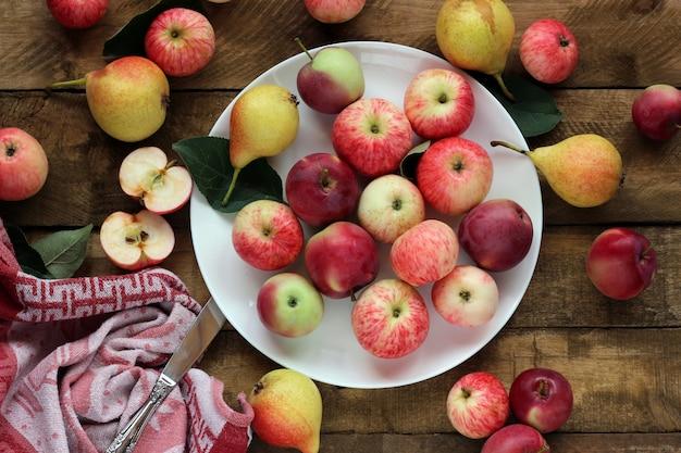 Reife äpfel und birnen auf dem tisch, draufsicht. tischstillleben.
