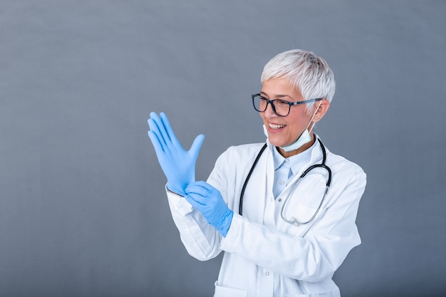 Reife ärztin, die schutzhandschuhe und medizinische schutzmaske anzieht, isoliert an der wand. doktor zieht sterile handschuhe an