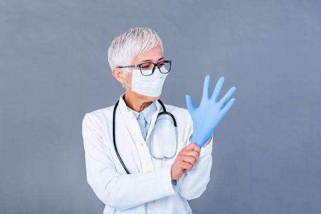Reife ärztin, die schutzhandschuhe und medizinische schutzmaske anzieht