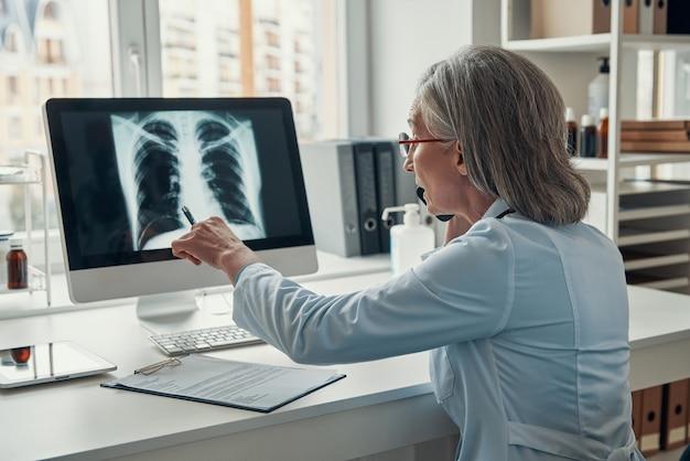 Reife ärztin im weißen laborkittel, die am telefon spricht und die lunge mit dem computer untersucht, während sie in ihrem büro sitzt