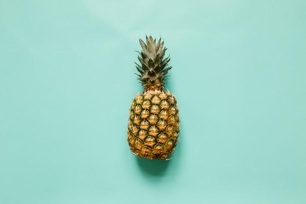 Reife ananas auf türkisfarbenem hintergrund lokalisiert. trendiges tropisches konzept des minimalistischen stils. platz für text, kopie, schriftzug.