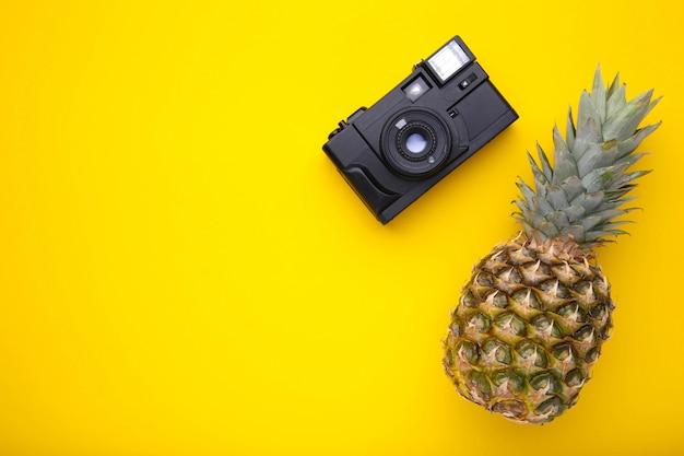 Reife ananas mit kamera auf gelb
