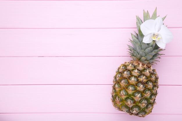 Reife ananas mit orchidee auf einem rosa hintergrund mit kopienraum