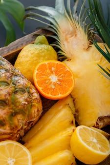 Reife ananas. tropische früchte mix holzkiste. mandarinen orangen ananas zitronen. geschnittener tropischer zitrusvitaminnachtisch als sommerhintergrund. hochwertiges archivfoto