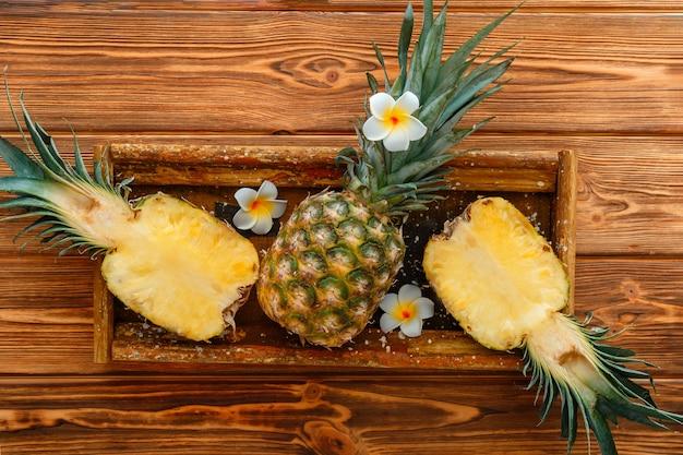 Reife ananas. tropische sommerfruchtananashälften und ganze ananas auf braunem dunklem tisch in holzkiste mit tropischen plumeriablumen. flach liegen. hochwertiges archivfoto