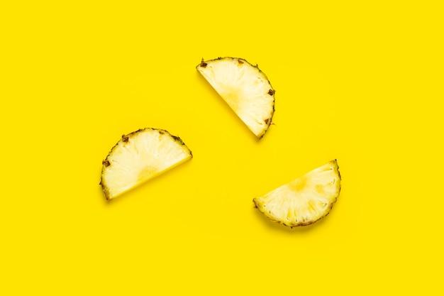 Reife ananasscheiben auf gelbem grund. ansicht von oben, flach.