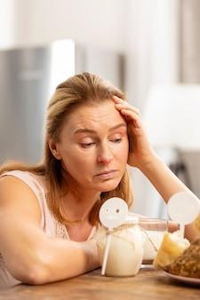 Reife ansprechende blonde frau, die von starken nahrungsmittelallergien müde ist