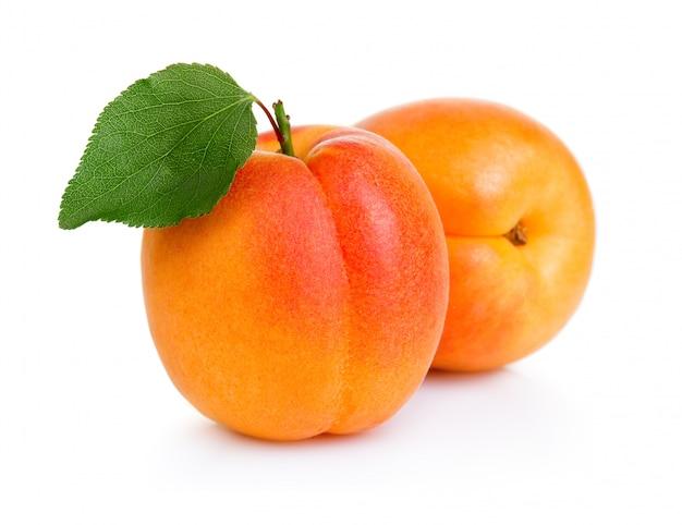 Reife aprikose trägt mit dem grünen blatt früchte, das auf weiß lokalisiert wird