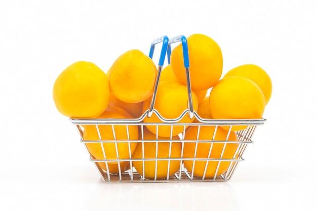Reife aprikosen in einem einkaufskorb aus einem supermarkt auf weißem hintergrund